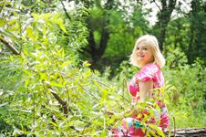 Free Adorable Blond Woman Sits On A Log In The Forest Stock Photography - 20720052