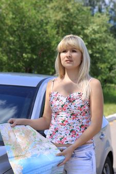 The Girl By The Car Searches For Road On A Map Stock Photography
