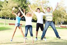 Family Jumping High In The Air On A Green Meadow Stock Photos
