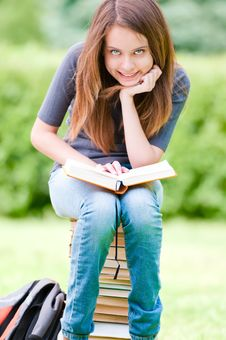 Free Happy Student Girl Sitting On Pile Of Books Stock Photo - 20734000