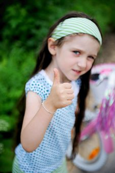 Free Long-haired Child Girl Poses With Thumbs Up Stock Photography - 20757732