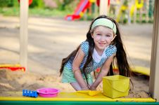 Happy Child Girl Is Playing In A Sandbox Stock Photo
