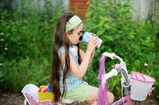 Free Long-haired Child Girl Drinks While Riding Bike Stock Photo - 20757830