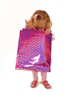 Little Girl Looking Into A Pink Shopping Bag