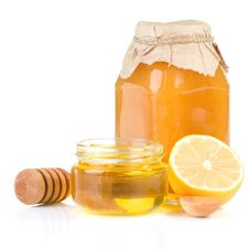 Jar Full Of Honey And Lemon On White