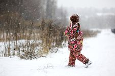 Child Girl In Colorful Snowsiut Plays In Snow Stock Images