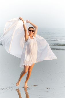 Woman Is Running On The Beach With White Shawl Stock Photos