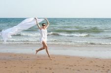 Woman Is Running On The Beach With White Shawl Stock Photo