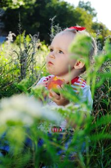 Baby With Peach On The Meadow Royalty Free Stock Photography