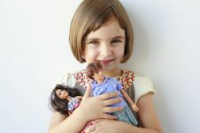 Free Little Girl Holding Boy And Girl Dolls Royalty Free Stock Photo - 20853595