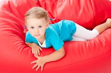 Free Child In Blue Shirt On Red Pouf Chair Royalty Free Stock Photos - 20875278