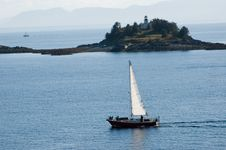 Sailboat Near Island Lighthouse Stock Photos
