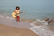 Free Happy Girl Jumping With Guitar On Beach Stock Image - 20905281