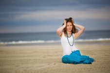 Beautiful Young Woman Sits On Sand Near The Ocean Stock Images