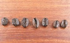 Free Coffee Beans Lined Up On A Wooden Floor Stock Image - 20931681
