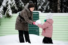 Young Mother And Daughter Have Fun In The Snow Stock Photo