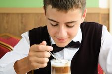 A Teenager Boy Enjoying Coffee In A Cafe Royalty Free Stock Image