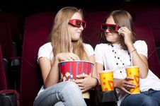 Two Beautiful Girls Watching A Movie At The Cinema Royalty Free Stock Photography