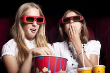 Two Beautiful Girls Watching A Movie At The Cinema Stock Photos