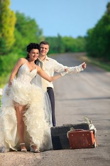 Newlywed Couple Hitchhiking On A Road Royalty Free Stock Photography
