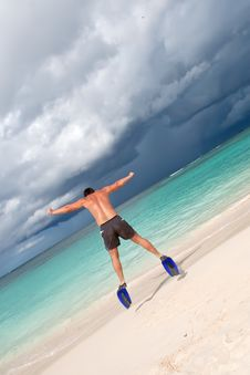 Tanned Man Jump In Blue Flippers On Sand Beach Stock Photography