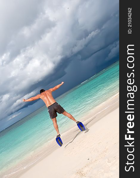 Tanned man jump in blue flippers on sand beach