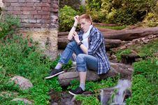 Young Human Is Siting Among Greenery Royalty Free Stock Image