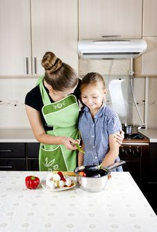 Free Woman With A Daughter In The Kitchen Preparing Stock Image - 21099621