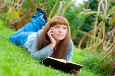 Free Young Woman Reading A Book Lying On The Grass Royalty Free Stock Image - 21106426