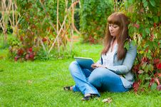 Young Woman Reading In Tablet Pc Stock Photo