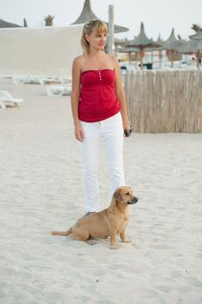 Young Woman Playing With Her Dog On The Beach. Stock Images