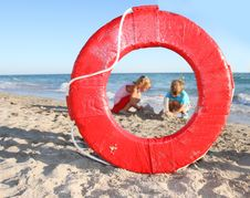 Children Playing On Beach, View Through Lifesaver Stock Photo