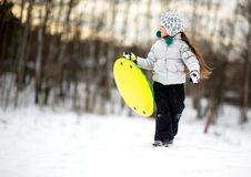 Cute Little Girl Running In The Snow With Saucer Royalty Free Stock Photos