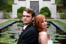 Bride, Groom Sitting By Lily Pond Stock Images