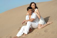 Couple In A White Dress Sitting On Sand Royalty Free Stock Photos
