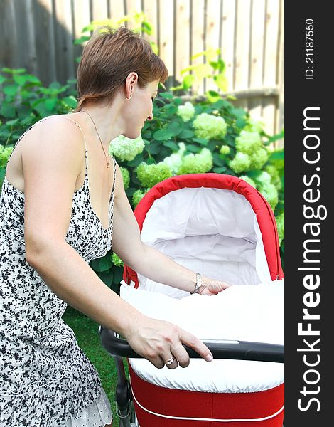 Beautiful woman looking in baby stroller