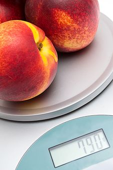 Peaches On The Scales On A White Stock Images