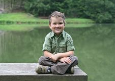 Free Boy Cross-legged On A Bench At Pond Royalty Free Stock Photos - 21194558