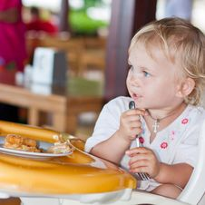 Adorable Baby Eating Cake In A Chair Stock Images