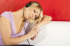 Free Attractive Young Woman On A Sofa With Headphones Royalty Free Stock Images - 21244809