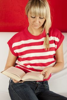 Free Young Woman Sitting On A Sofa Reading Book Royalty Free Stock Images - 21244879