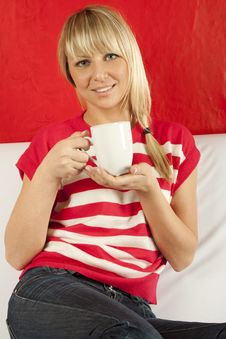 Young Woman Sitting On A Sofa Drinking Coffee Stock Photography