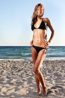 Young Woman In Black Bikini On Sky Background Royalty Free Stock Image