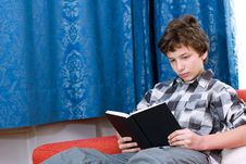 Pre-teen Boy Reading  Book On Couch Stock Images