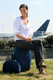 Free Young Woman Seated On Luggage Royalty Free Stock Photography - 21257467