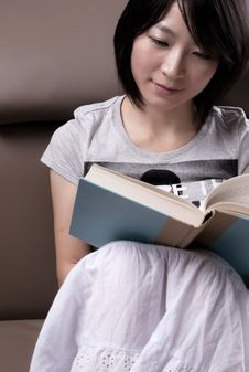 Young Woman Sitting On Sofa Reading Book Stock Photo