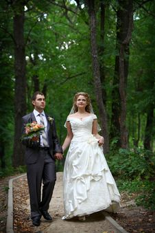 Bride And Groom Walking In Forest Stock Photography