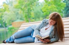 Free Young Woman Reading A Book Sitting On The Bench Royalty Free Stock Photography - 21297037