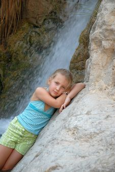 Child Girl On The Background Of A Waterfall Poses Stock Photography
