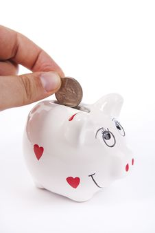 Hand Putting Money In A Piggy Bank Royalty Free Stock Images